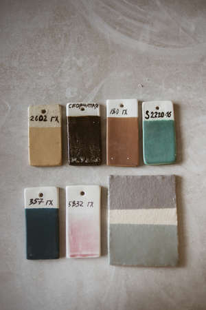 Top view on colored glazed ceramic samples on grey table in workroom Standard-Bild
