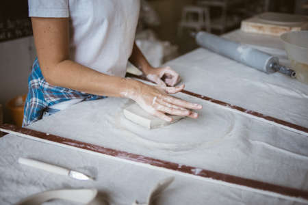 Sculptor prepares grey raw clay for modeling ceramic plate on big table with industrial fabric in workshop Standard-Bild