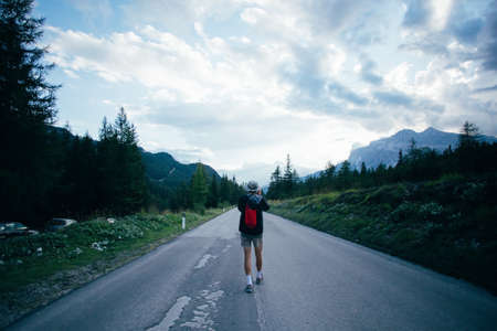 Solo millennial nomad photographer influencer path finder walks on empty road high in mountains during beautiful sunset, makes photo of skies and landscape