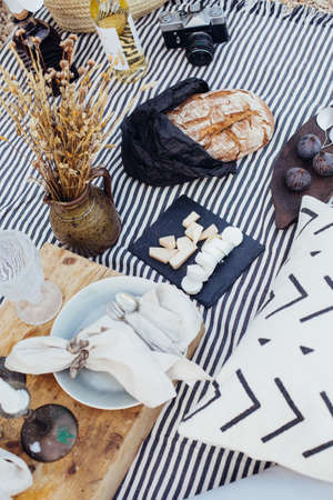 Natural fresh and organic products, cheese, wine, bread and figs arranged for romantic getaway for couple, on picnis blanket with pillows and candles and vintage decoration