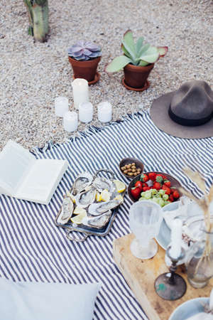 Still life of romantic chic setup for picnic blanket table with candles, flower decoration, fruits and strawberries in bowl, novel book and fresh seafood oysters