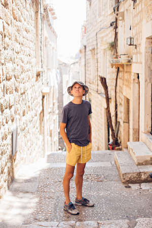 Handsome attractive young man in yellow shorts and  hat, walks around old european town in summer heat, explores ancient tourist attractions