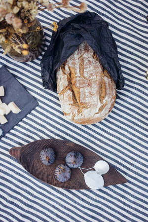 Top view on designer perfect arrangement withfigs on wooden plate, artisan sour dough bakery bread and cheese plate, idyllic atmosphere of rustic vintage farm style