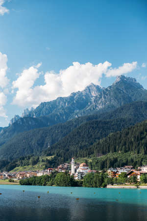 View over beautiful pristine italian village lost high in mountains, with tremendous huge rock range over old town, blue skies with white clouds over dolomites