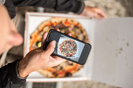 Social media influencer millennial hipster taking photo of his fresh pizza