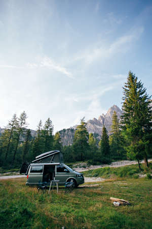 Small travel vehicle camping van or big car with folding rooftop with bed is parked on secluded wild site under huge mountain formation in dolomites, surrounded by forest Фото со стока