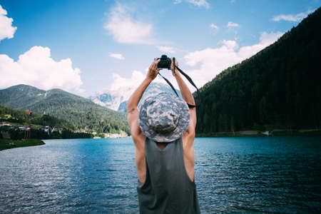 Young man in tan top and hat makes photos with digital mirrorless camera of alpine lake with blue water and mountains, nomad explorer and hipster millennial