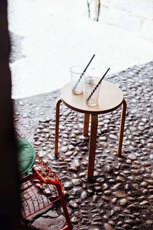 Two empty glasses or jars of coffee, juice or lemonade with straws stand symmetrically on wooden table in front of cafe or bar in old town of dubrovnik