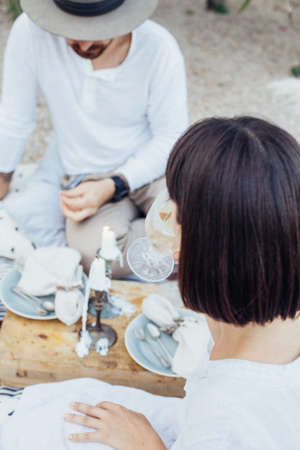 Soft focus shot of beautiful hipster couple on chic romantic date or wedding or engagement proposal, they drink wine, laugh and flirt, eat snacks and fruits