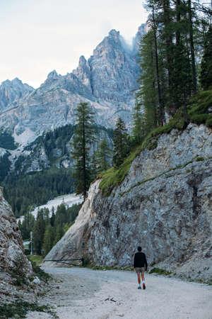 Curious explorer male figure of adventurer nomad traveler walks on path inbetween mountains and forest high in italian dolomites Standard-Bild