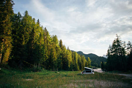 Empty wild camping site lost in green forest on early morning or sunset, with white travel van camped out with folding roof, concept nomad life off grid, adventures