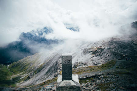 Structure made of stone and bricks to commemorate or signal top of summit on mountain covered with clouds, alps or dolomites, exploration and hiking guide