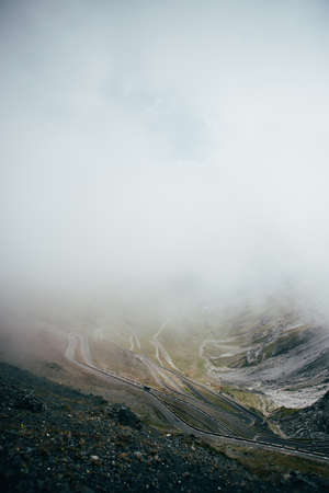 Winding road with switchbacks and hairpin turns climbing up side of mountain of stelvio pass in italian dolomites lost in clouds or fog, concept travel, adventure