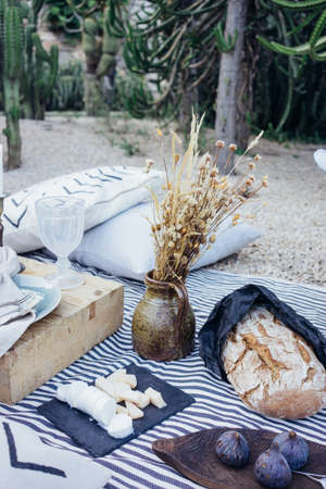 Beautiful arranged table in park for date or dinner or picnic, with jar of flowers, cheese set variety, figs, artisan home made bread, ideal setup for rustic wedding Standard-Bild