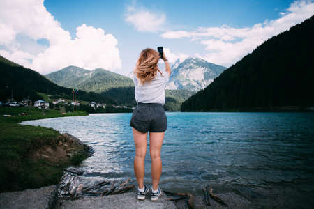 Young female tourist millennial adventurer stands on shore of beautiful pristine lake high in mountains with turquoise water, she makes photo on her smartphone for memories of travel