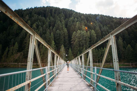 Young fit adventurer man with camera makes photo of nature, stands in middle of metal pedestrian bridge over pristine blue water lake that connects two shores, forest and city