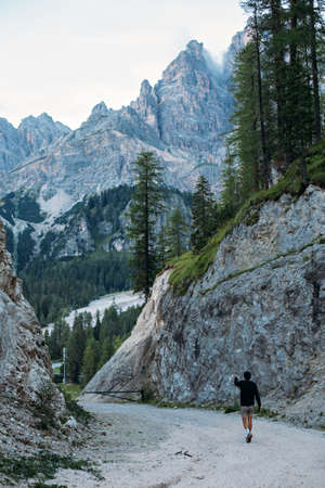 Curious explorer male figure of adventurer nomad traveler walks on path inbetween mountains and forest high in italian dolomites Фото со стока