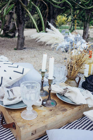 Still life arrangement for outdoors picnic or romantic surprise getaway with antique vintage wood tray,wine glasses, candles and floral decorations make for perfect date