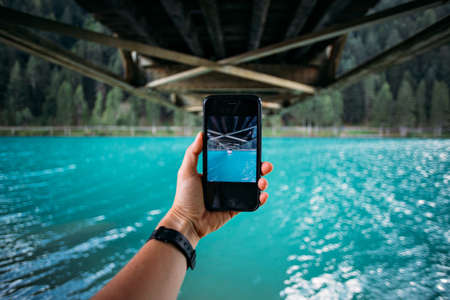 POV of hand holding smartphone and making photo of turquoise lake and bridge metal construction for share on social media channels, concept millennial nomads Standard-Bild