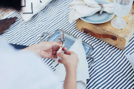 Close up soft focus shot of female decorator or florist preparing decorations for setting up picnic or restaurant dinner table with napkin, ceramic vintage plates and flowers Standard-Bild