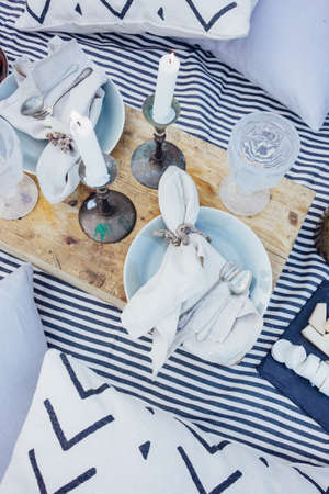 Top view on beautiful arranged table or picnic blanket, with aged antique wooden tray, pillows, candles, vintage cutlery and ceramic plates, decorated with candles