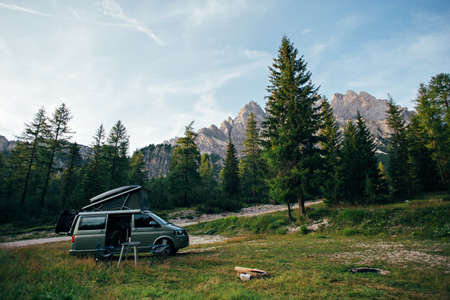 Small travel vehicle camping van or big car with folding rooftop with bed is parked on secluded wild site under huge mountain formation in dolomites, surrounded by forest Standard-Bild