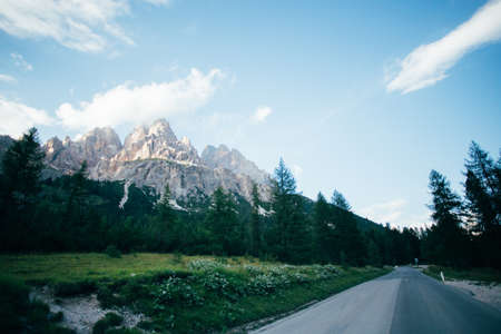 Beautiful sunset over high altitude mountain road next to famous peak in italian dolomites Tre Cime de Lavaredo, famous for rocky formations and snow in summer Фото со стока