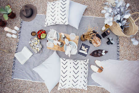 Top view on picnic blanket layout with fresh artisan bread, wine, cheese, fruits and oysters, with wooden tray and pillows with candles around for romantic amorous style