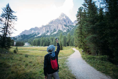 Young urban adventurer with small light backpack stands on path of beginning of hiking trail and makes photo of amazing epic mountain peak in middle of forest Standard-Bild