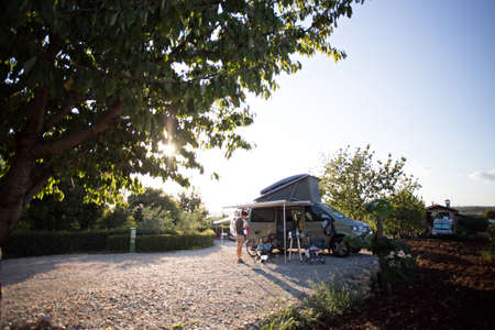 Young tourist explorer stands next to camping van in beautiful french provence vineyard on sunset evening, concept vacation, nomad life of adventure