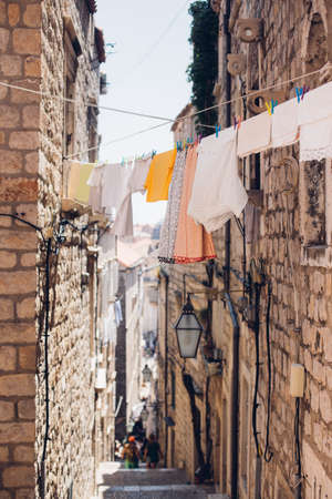 Laundry hangs to dry in narrow street of medieval mediterranean town, paved with bricks and old vintage light hangs from building, summer tourists walk in distance Standard-Bild