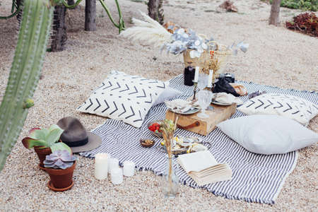 Top view on still life outdoor picnic blanket setup for romantic day or night out for hipster stylish couple, wedding, proposal happening with candles and chic snacks