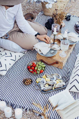 Unrecognizable man in hat, with arm tattoos sits on ground in park in romantic chic picnic as surprise, with tasty olives and oysters, strawberries