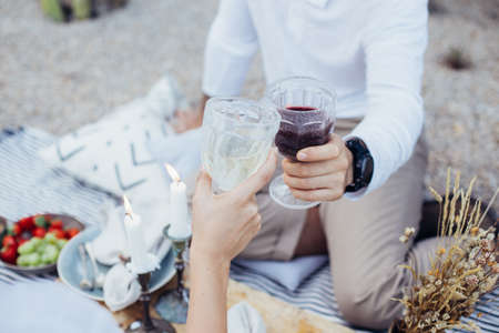 Beautiful people enjoy drinks, red and white wine on picnic date in beautiful setting. Romantic getaway for engagement or proposal, refreshing alcohol beverages