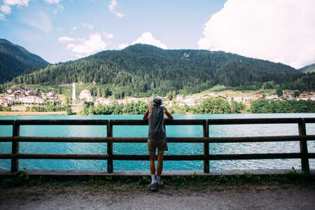 Attractive fit healthy skinny man in cool fashionable outfit of adventurer and explorer, stands next to fence and looks at blue mountain lake and italian village