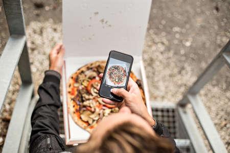 소셜 미디어 영향력 밀레니엄 힙 스터는 자신의 스마트 폰에서 찍은 피자를 팔로우와 온라인으로 공유하기 위해 상자에서 꺼낸 신선한 뜨거운 사진을