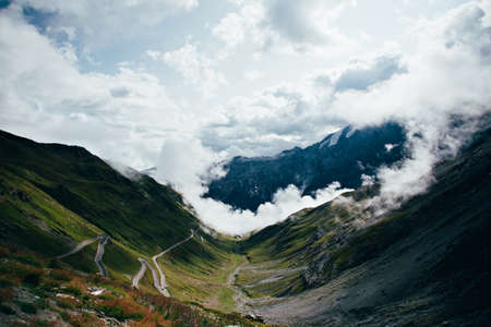 Shot from top of Stelvio pass between Italy and Switzerland on sunny day, standing above clouds and overlooking hairpins and sharp turns that lead to summit Фото со стока