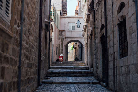 Narrow steep street of beautiful ancient european village or city, Dubrovnik Croatia with cobbled paved walls and floors. Lonely lost tourist sits on steps, exploring
