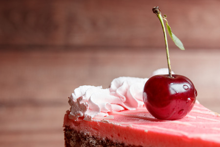 Chocolate cake with cherries on wooden background. Reklamní fotografie