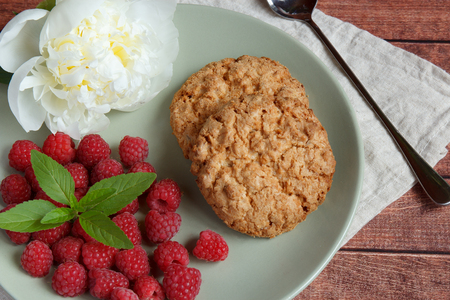 stuffing: Delicious cookies with raspberries and mint and white peony flower on the plate.