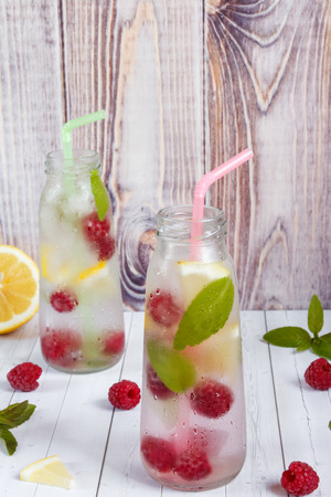 Cold cocktail with raspberries, lemon and mint. Wooden background.