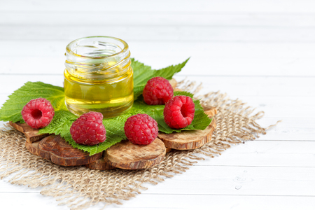 The bowl with honey, berries and leaves of raspberry on a wooden stand. Spoon with honey. Stock Photo