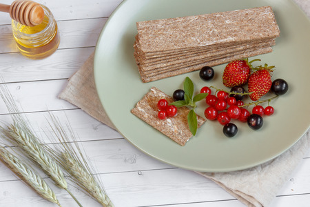 processed grains: Healthy Snack from Wholegrain Rye Crispbread Crackers and Fresh berries on the Light Background.