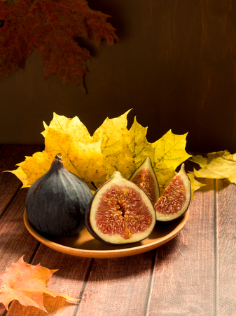 Fresh figs on a plate with yellow autumn leaves wooden rustic background. Banque d'images
