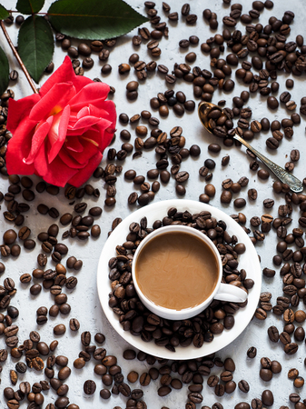 Blooming red rose coffee Cup, coffee beans on the background under the concrete. Stock Photo