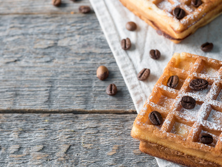 Soft Viennese Belgian waffles with powdered sugar and coffee beans on rustic wooden background.