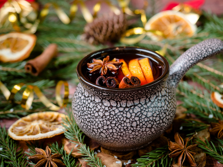 Christmas mulled wine with cinnamon, orange and star anise in a ceramic bowl with winter decorations.