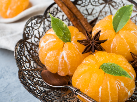 Fresh mandarins in a plate with fir tree branches, star anise cinnamon on gray background. Stock Photo