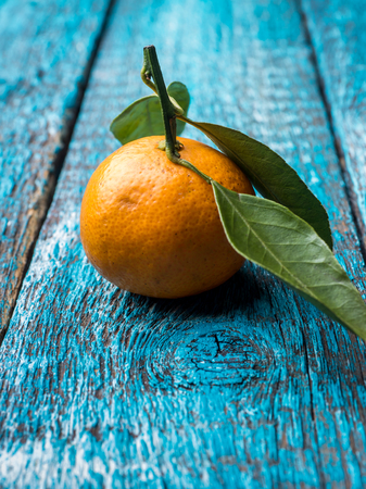 Fresh Mandarin or tangerine with stems and leaves on blue wooden background copy space.