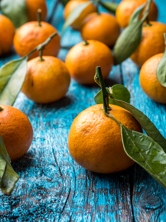 Fresh Mandarin or tangerine with stems and leaves on a blue wooden background flat lay. Stock Photo